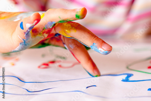 Obraz Close up young girl painting with colorful hands. Art,  creativity and painting concept. - fototapety do salonu