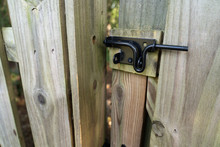 Black Metal Latch On A Wooden Privacy Fence In A Residential Back Yard.
