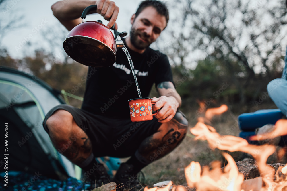 Fototapety, obrazy: Young male making tea, hanging out at campsite