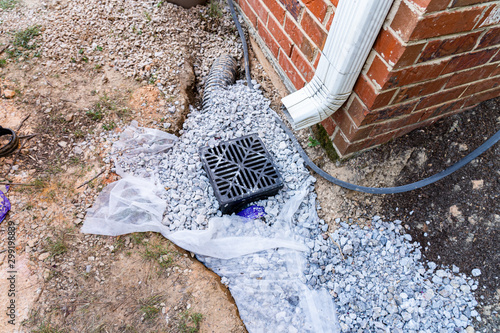Photo Plastic catch basin installed under a downspout to alleviate drainage issues aga