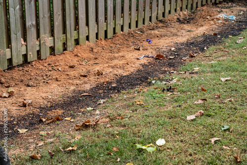 Dirt backfills this trench housing a French drain in a backyard DIY project to a Canvas Print