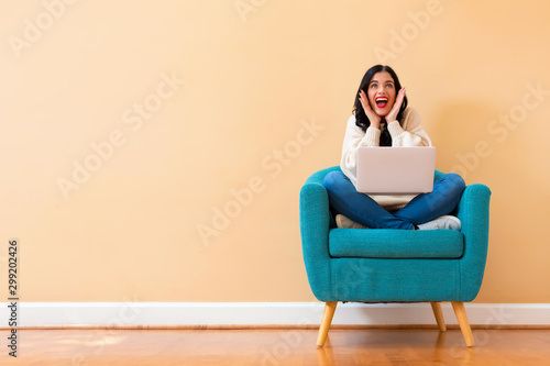 Spoed Fotobehang Wanddecoratie met eigen foto Surprised young woman using a laptop computer sitting in a chair