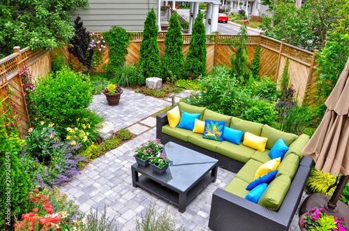 A beautiful small, urban backyard garden featuring a tumbled paver patio, flagstone stepping stones, and a variety of trees, shrubs and perennials add colour and year round interest Wallpaper Mural