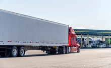 Red Big Rig Semi Truck Transporting Cargo In Dry Van Semi Trailer Running On The Truck Stop To Fuel Station For Refuel And Continue Delivery