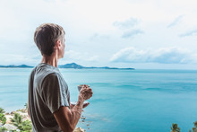 Young Man Standing Near The Window With Coffee Cup And Enjoying A View To The Ocean On The Tropical Island