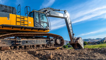 Panorama Frame Yellow Excavator With Continuous Tracks Digging Soil At A Construction Site