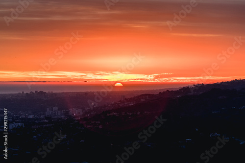 Sunset glowing over hills and city landscape.
