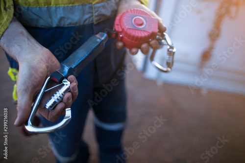 Male inspector hand testing opening locking carabiner gate which connecting with Tableau sur Toile