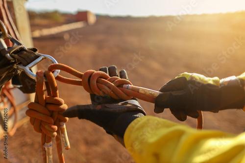 Fotografía  Rope access technician inspector wearing black glove inspecting figure of eight