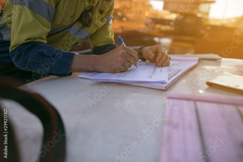 Canvas Print Construction supervisor holding a pen signing issuing safety permit to work on t