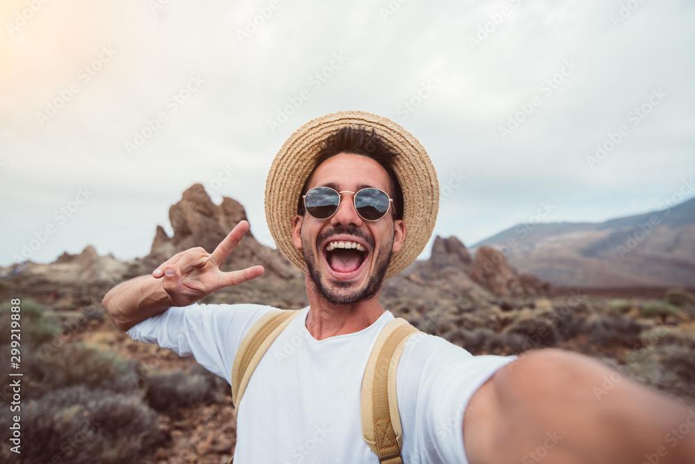 Fototapeta Handsome hiker taking a selfie hiking a mountain using his smartphone
