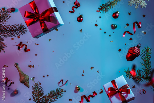 Fototapeta  Christmas card made of flying decorations, gift boxes, fir branches, balls, sparkles and confetti on colorful neon blue and purple background
