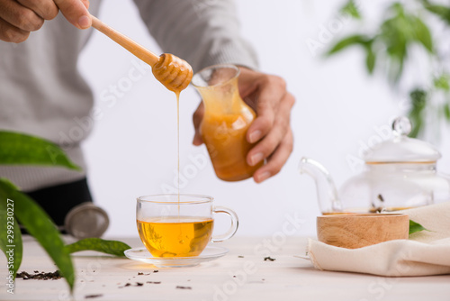 Spoed Foto op Canvas Thee Cropped image of arista pouring honey into cup of tea