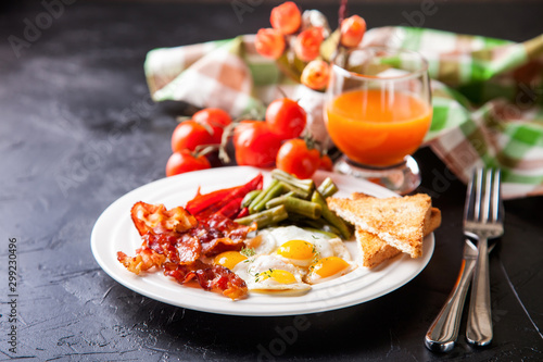 breakfast - fried eggs, haricot, a paprika and bacon in a plate, selective focus Fototapet