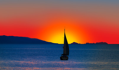 Fototapeta Wschód / zachód słońca Yacht sailing against sunset