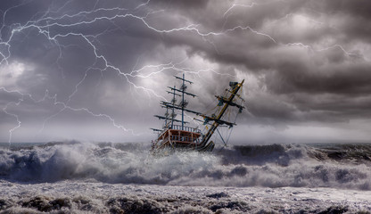 Sailing old ship in storm sea against heavy sunset clouds