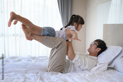 Obraz na plátne  father and daughter enjoy playfull together in house bedroom at comfortable time