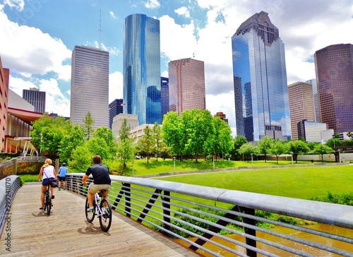 Fotomural Bicyclists cross wooden bridge in Buffalo Bayou Park, with a beautiful view of d
