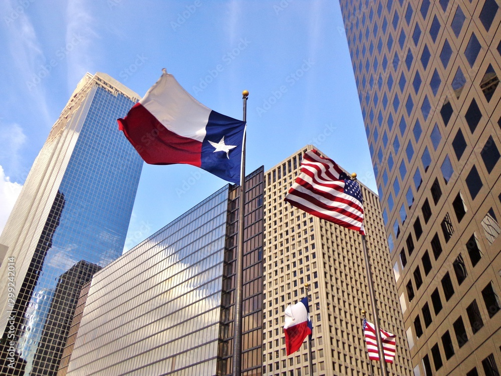 Fototapeta Low angle view of United States of America flag and Texas state flag in front of modern skyscrapers in downtown Houston (skyline / skyscrapers) on a summer day - Houston, Texas, USA