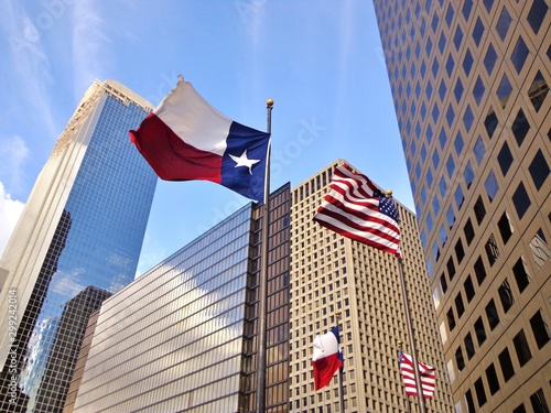 La pose en embrasure Amérique du Sud Low angle view of United States of America flag and Texas state flag in front of modern skyscrapers in downtown Houston (skyline / skyscrapers) on a summer day - Houston, Texas, USA