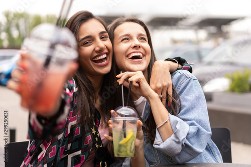Carta da parati  Hipster girlfriends drink cocktail in urban city background