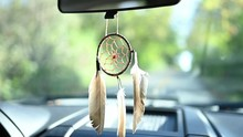 Dream Catcher Attached To The Rearview Mirror Of A Pickup Truck. The Focus Is On The Feather-adorned Dream Catcher As The Truck Drives Down The Road. Excellent B-roll Indicating Country Driving