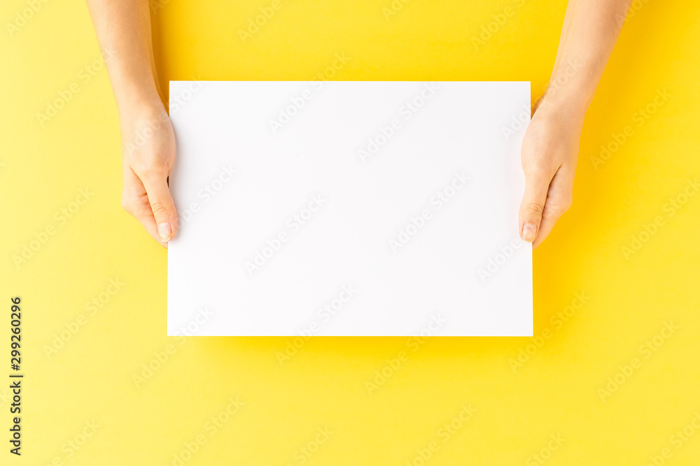 Fototapety, obrazy: Overhead shot of woman's hands holding blank paper sheet on yellow table. Close up