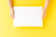 canvas print picture - Overhead shot of woman's hands holding blank paper sheet on yellow table. Close up