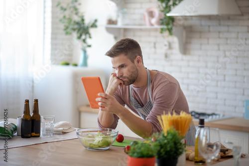 Fotografía  Bearded husband watching culinary video on tablet