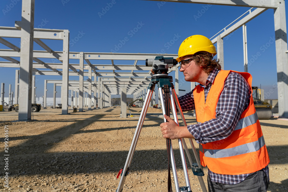 Fototapety, obrazy: Mature Land Surveyor Looking Through Tacheometer on Construction Site