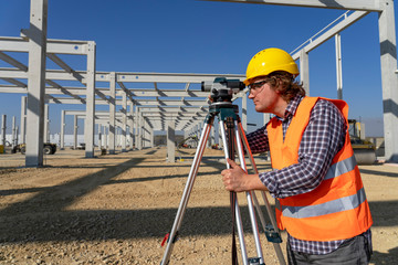 Fototapeta na wymiar Mature Land Surveyor Looking Through Tacheometer on Construction Site