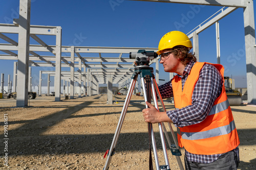 Mature Land Surveyor Looking Through Tacheometer on Construction Site - 299261671