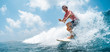 canvas print picture Young caucasian man surfs the ocean wave and makes a lot of splashes into the camera. Chickens surf spot in Maldives