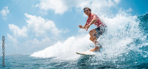 Young caucasian man surfs the ocean wave and makes a lot of splashes into the camera Canvas Print