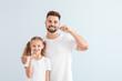 Leinwandbild Motiv Portrait of father and his little daughter brushing teeth on light background