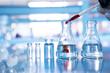 Leinwandbild Motiv orange drop in glass flask with vial and chemical molecular on blue science laboratory background