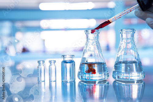 orange drop in glass flask with vial and chemical molecular on blue science laboratory background - 299269200