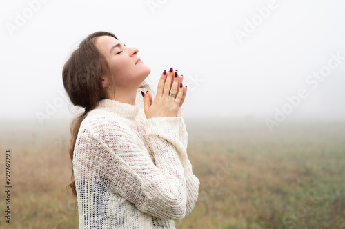 Girl closed her eyes, praying in a field during beautiful fog Tablou Canvas