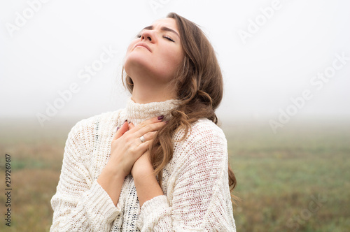 Girl closed her eyes, praying in a field during beautiful fog Fototapeta