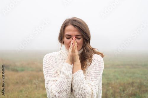 Fototapeta  Girl closed her eyes, praying in a field during beautiful fog
