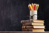 Stack of vintage books, eyeglasses and pencils, education and learning