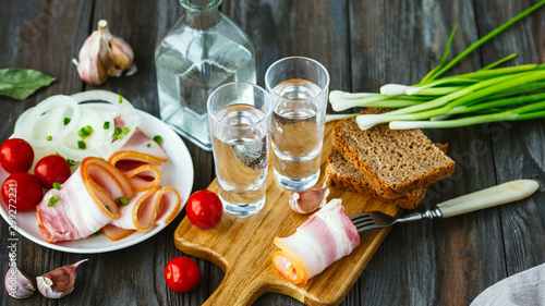 Foto auf Leinwand Alkohol Vodka with lard and green onion on wooden background. Alcohol pure craft drink and traditional snacks, tomatos and bread toast. Negative space. Celebrating food and delicious.