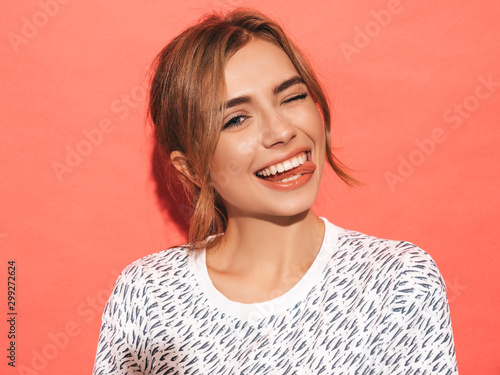 Obraz Young beautiful woman looking at camera. Trendy girl in casual summer shirt clothes with natural makeup. Positive female smiling. Funny model posing near pink wall in studio.Shows tongue and winks - fototapety do salonu