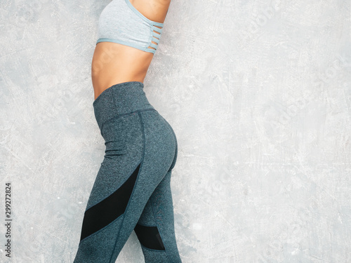 Spoed Fotobehang Ezel Portrait of fitness woman in sports clothing looking confident.Young female wearing sportswear. Beautiful model with perfect tanned body.Female posing in studio near gray wall