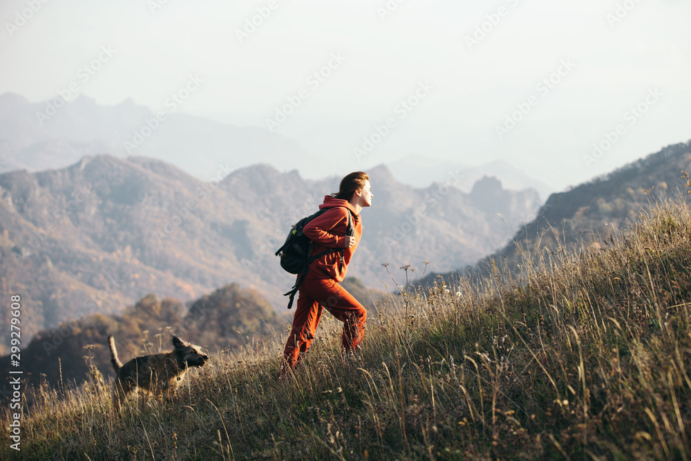 Fototapety, obrazy: Beautiful woman traveler climbs uphill with a dog on a background of mountain views. She is with a backpack and in red clothes.