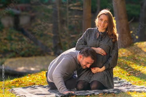 Young husband listening for a foetal heartbeat Fototapeta