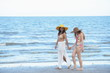 Two beautiful girls in Swimwear for a walk on the beach happily