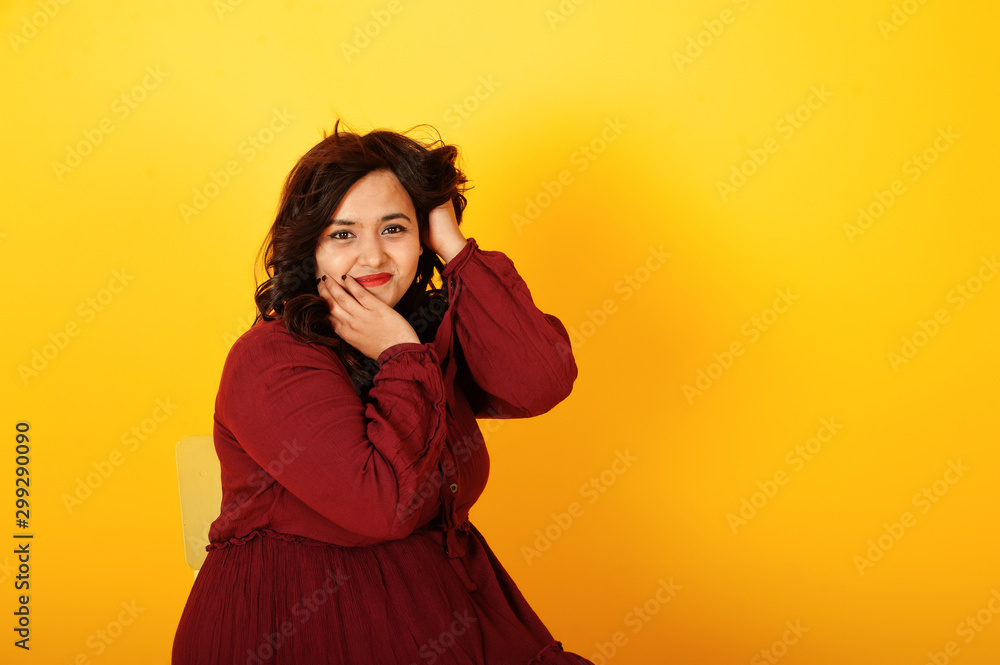 Fotografía  Attractive south asian woman in deep red gown dress posed at studio on yellow background and sitting on chair