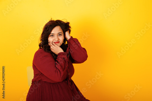 Pinturas sobre lienzo  Attractive south asian woman in deep red gown dress posed at studio on yellow background and sitting on chair