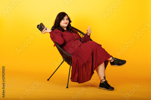 Attractive south asian woman in deep red gown dress posed at studio on yellow background sitting on chair with old vintage photo camera Canvas Print